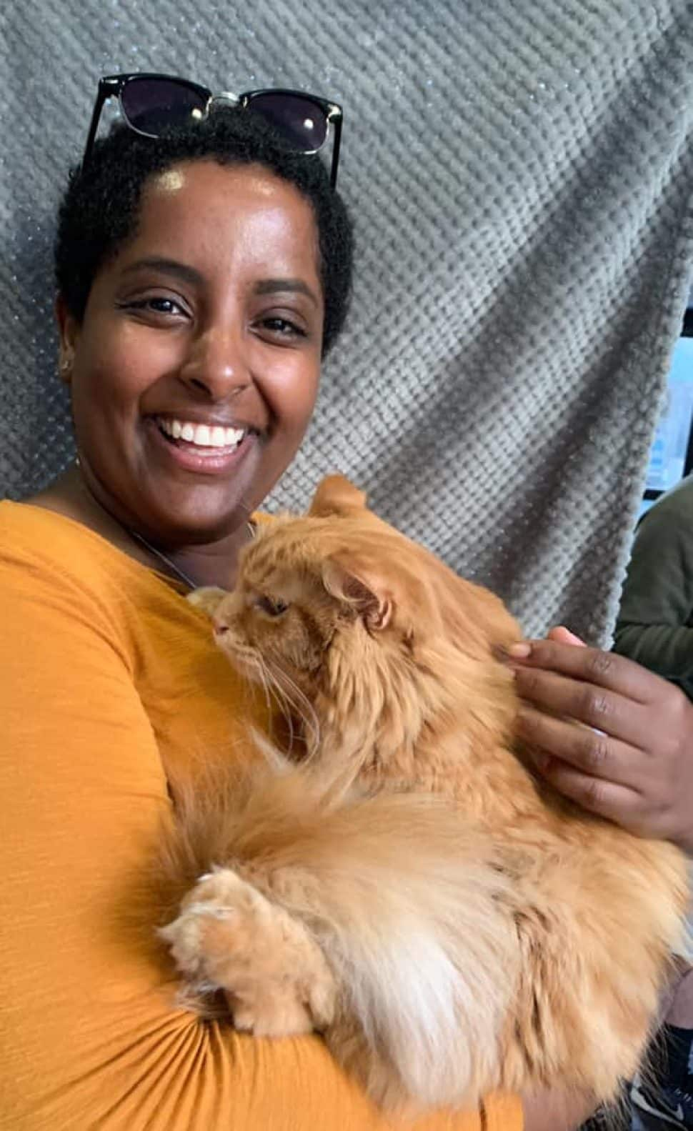 Woman with short black hair and sunglasses on top of her head, wearing a bright-orange shirt, cuddles newly adopted orange cat.